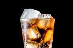 Vetro di soda con il cubetto di ghiaccio isolato sul nero fotografia stock
