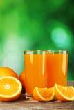 Vetro di succo d'arancia fresco su fondo di legno grigio Fotografia Stock