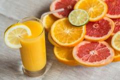 Vetro di succo d'arancia su un fondo di tela con le fette di agrume Fotografie Stock