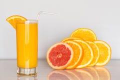 Vetro di succo d'arancia sui precedenti bianchi con le fette di agrume Immagine Stock