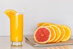 Vetro di succo d'arancia sui precedenti bianchi con le fette di agrume Fotografie Stock Libere da Diritti