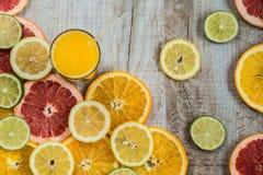 Vetro di succo d'arancia sui precedenti di legno con le fette di agrume Immagini Stock Libere da Diritti