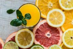 Vetro di succo d'arancia sui precedenti di legno con le fette di agrume Fotografie Stock Libere da Diritti