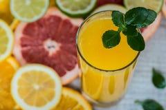 Vetro di succo d'arancia sui precedenti di legno con le fette di agrume Immagine Stock
