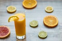 Vetro di succo d'arancia sui precedenti di legno con le fette di agrume Fotografie Stock