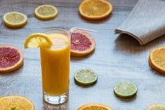 Vetro di succo d'arancia sui precedenti di legno con le fette di agrume Fotografia Stock