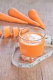 Vetro di succo, delle carote e del centimetro casalinghi sopra Fotografia Stock