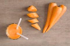 Vetro di succo e delle carote casalinghi sul bordo di legno Fotografia Stock