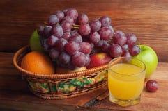 vetro di succo e di frutta in un canestro di vimini Fotografie Stock