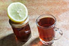 Vetro di tè con la fetta di limone e di bottiglia di miele Immagini Stock Libere da Diritti