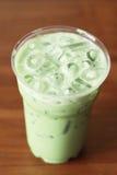 Vetro di tè verde latteo su fondo di legno Immagine Stock