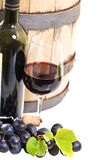 Vetro di un vino rosso, di una bottiglia, di un barilotto e di un'uva Fotografie Stock Libere da Diritti