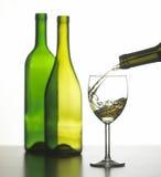 Vetro di vino bianco con due bottiglie di vino verdi Fotografia Stock Libera da Diritti