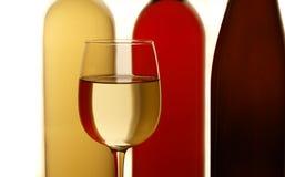 Vetro di vino bianco con le bottiglie nella priorità bassa Immagine Stock