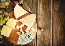 Vetro di vino bianco, di formaggio, dei dadi e dell'uva Fotografie Stock