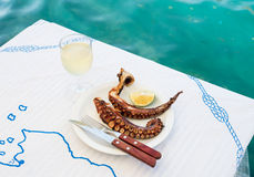 Vetro di vino bianco e del polipo arrostito su una tavola alla costa di mare Fotografie Stock
