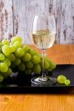 Vetro di vino bianco e un mazzo di uva Fotografia Stock