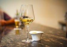 Vetro di vino bianco sulla barra lunga accanto al gufo dei dadi Immagini Stock Libere da Diritti