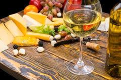 Vetro di vino bianco sulla Tabella con formaggio e frutta fotografie stock