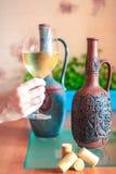 Vetro di vino bianco in una mano del ` s della donna fotografie stock libere da diritti