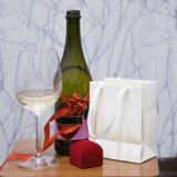 Vetro di vino, bottiglia decorata con l'arco del nastro Contenitore di gioielli, regalo di festa sulla tavola woodern Immagine Stock