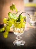 Vetro di vino con uva luminosa su un ramo e sulle foglie su una fine di legno scura del fondo su fotografia stock