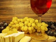 Vetro di vino della natura morta dell'uva, specialità gastronomiche di legno della tavola fotografie stock