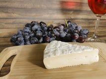 Vetro di vino della natura morta dell'uva, tavola di legno immagine stock