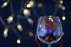 Vetro di vino di vetro con i giocattoli di Natale Immagine Stock Libera da Diritti