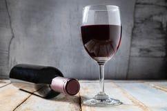 Vetro di vino e bottiglia di vino su vecchio fondo di legno immagini stock libere da diritti