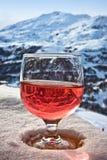 Vetro di vino e del paesaggio delle alpi di inverno Fotografie Stock
