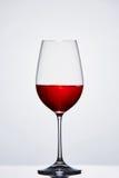 Vetro di vino puro del vino pieno a metà con vino rosso contro fondo leggero con la riflessione Immagine Stock Libera da Diritti