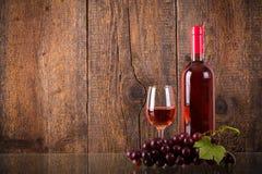 Vetro di vino rosato con l'uva su vetro Immagini Stock