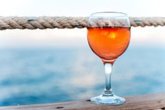 Vetro di vino rosato molle fresco sul pilastro di legno Immagini Stock