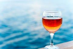 Vetro di vino rosato molle fresco sul pilastro di legno Fotografia Stock