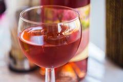 vetro di vino rosato sul fondo della bottiglia di vino fotografie stock libere da diritti