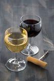 Vetro di vino rosso bianco e su un fondo di legno scuro Immagini Stock Libere da Diritti