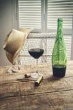 Vetro di vino rosso che sta sulla tavola con il cappello di paglia fotografia stock libera da diritti