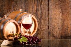 Vetro di vino rosso con due barilotti ed uva Immagine Stock