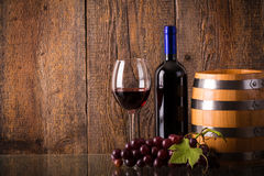 Vetro di vino rosso con l'uva del barilotto della bottiglia su vetro Immagini Stock