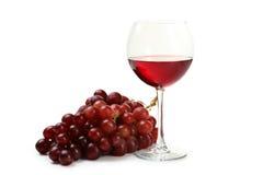 Vetro di vino rosso con l'uva isolata su un bianco Fotografia Stock