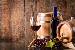 Vetro di vino rosso con la bottiglia ed i barilotti scuri Immagine Stock