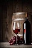 Vetro di vino rosso con la condizione del barile e della bottiglia Fotografia Stock Libera da Diritti
