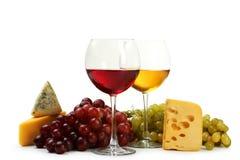 Vetro di vino rosso e bianco, di formaggi e dell'uva isolati su un bianco Immagine Stock