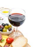 Vetro di vino rosso e degli aperitivi - formaggio, pane, salame, olive Fotografie Stock
