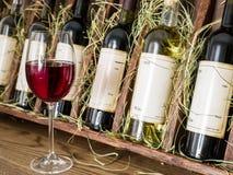 Vetro di vino rosso e delle bottiglie di vino Immagini Stock Libere da Diritti