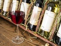 Vetro di vino rosso e delle bottiglie di vino Fotografia Stock