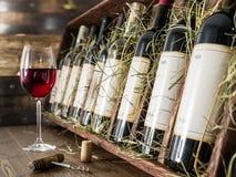 Vetro di vino rosso e delle bottiglie di vino Immagine Stock
