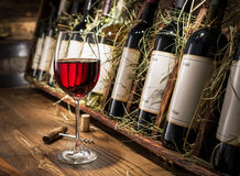Vetro di vino rosso e delle bottiglie di vino su un fondo Immagini Stock Libere da Diritti