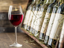 Vetro di vino rosso e delle bottiglie di vino su un fondo Immagini Stock
